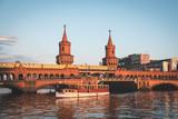 Oberbaumbruecke / Oberbaum Bridge and boat on river Spree in Berlin, Germany
