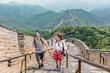 Happy couple tourists holding hands walking up the Great wall of china, top worldwide tourist destination. Young multiracial people travelers during Asia vacation.