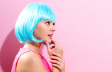Fototapety Portrait of a woman in a bright blue wig on a pink background