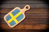 Concept of Swedish cuisine. Cutting board with a Sweden flag on a wooden background