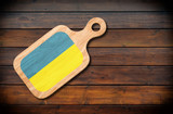 Concept of Ukrainian cuisine. Cutting board with a Ukraine flag on a wooden background