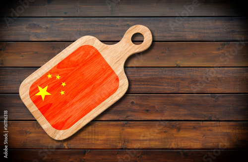 Concept of Chinese cuisine. Cutting board with a China flag on a wooden background