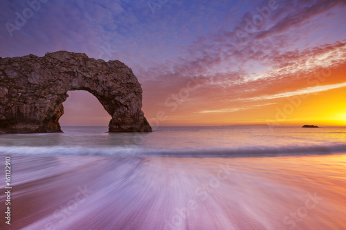 Durdle Door rock arch in Southern England at sunset Poster
