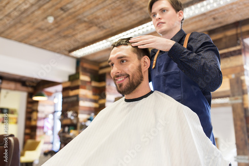 man and barber styling hair at barbershop