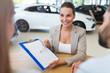 Female car dealer in showroom