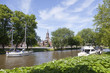boats in canal near centre of old dutch town leeuwarden with church in the background