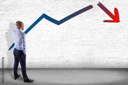 Businessman in front of a wall thinking about problem facing a business arrow breaking down - business concept