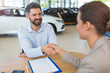 Car dealer shaking hand with a buyer
