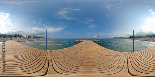 Poster View from a wooden pier on the sea and beach, mountains, sky