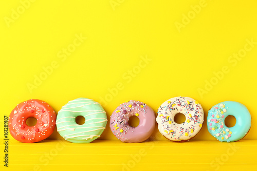 Tasty donuts with sprinkles on yellow background