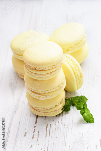Yellow macaroons on white wooden background.