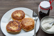 three pancakes on a white plate with sour cream on a dark table and small jar with jam. low angle view.