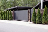 серо коричневые ворота и забор с декоративными зелёными деревьями перед асфальтированной дорогой  - 161345711