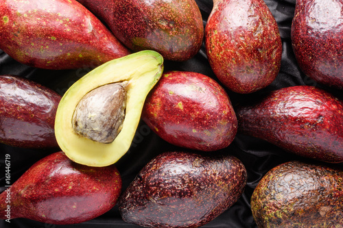Closeup view of fresh ripe avocados on dark background