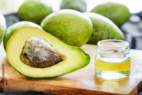 Fresh ripe avocado and natural avocado oil on wooden board