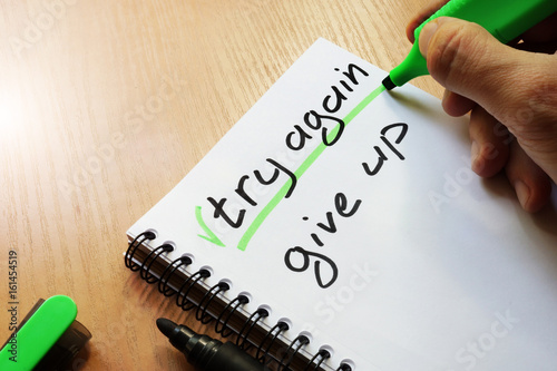 Try again or give up written by hand. Photo by designer491