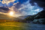fence through the grassy meadow in mountains time change concept