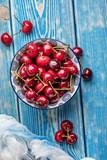 Fresh cherries in a blue bowl.