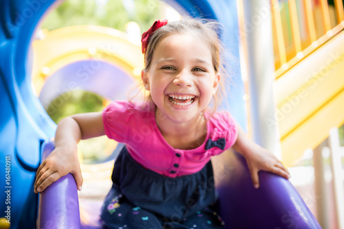Foto Murales Little Girl Playing At Playground Outdoors In Summer