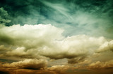 Fog and clouds looking up into a fantasy evening sky. Image looks antique, In orange and green colors