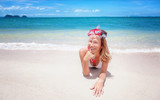 Beautiful young woman lies on a tropical beach with a snorkelling mask. Activities at the resort, sports and entertainment, vacation and travel concept - 161500335