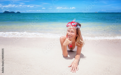 Beautiful young woman lies on a tropical beach with a snorkelling mask. Activities at the resort, sports and entertainment, vacation and travel concept