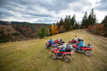 Group of five people driving quad bikes on the hillside at the background of autumn forest with colorful trees and mountains. Top view