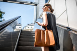 Young businesswoman with bag and phone getting up on the escalator during the business trip in the modern city - 161516988
