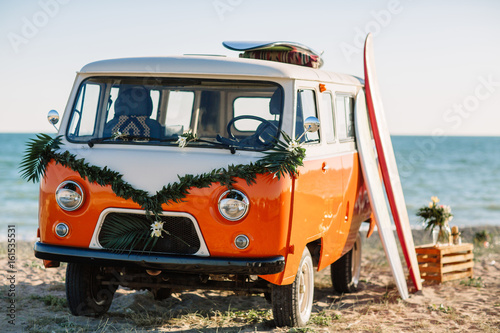 autobus z deską surfingową na dachu jest zaparkowany w pobliżu plaży