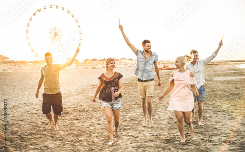 Group of happy friends having fun on the beach at sunset - Summer joy and friendship concept - Warm sunshine filtered color tone with focus on tall guy in the middle holding sparkle bengal fire candle - 161536172