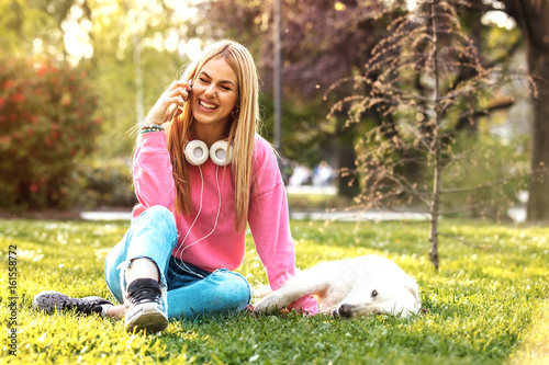 Woman enjoying park with dog Poster