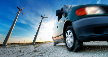 Industry of electric car and renewable energy concept. Wind mills and tire car detail. Electricity and ecology