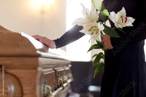 woman with lily flowers and coffin at funeral