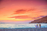 Two women taking photos of the amazing sunset at the beach of Matala, Crete, Greece.