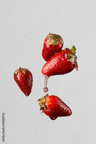 four strawberries and juice splash four strawberries isolated on a light-gray background - 161601770