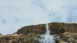 Majestic landscape, waterfall in Iceland. Half frozen melting after winter