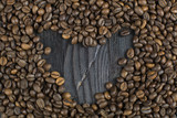 Coffee beans in the form of heart on a background of burnt, black wood