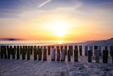 Sonnenuntergang in Zeeland am Strand mit Holzpfählen im Sand