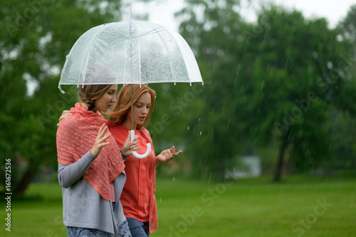 Two women walking park in rain and talk Poster