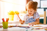 Fototapety child  girl draws with colored pencils