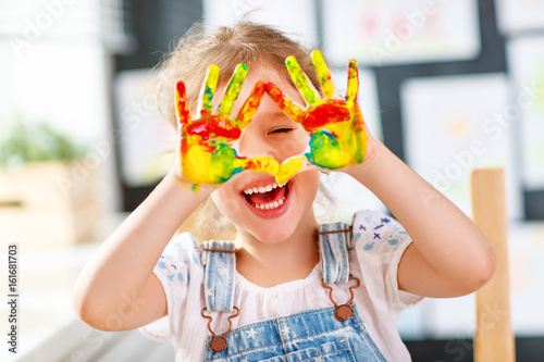 Leinwanddruck Bild funny child girl draws laughing shows hands dirty with paint