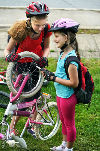 Bicycle tire pumping by child bicyclist. Girl repair bicycle on road . Kids pump up tire. Children return home from school on bicycles. Tone image.