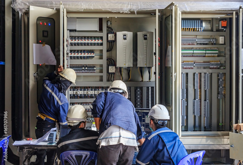 Engineer working on checking and maintenance equipment at wiring on PLC cabinet, Engineer checking status step up transformer