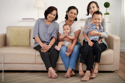 Portrait of  Asian family posing for photo at home, holding two children and  al Poster