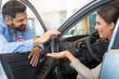 Woman receiving keys from a car dealer