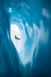 Man Rappelling past opening of blue ice cave on Matanuska Glacier, Alaska