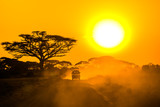 safari jeep driving through savannah in the sunset