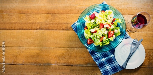 Fresh salad in bowl with red wine on wooden table