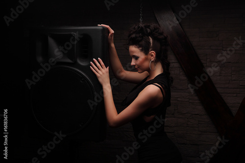 young girl in black clothes near big black speaker and listen to the music Poster