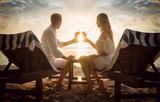 Paar mit Cocktails am Strand auf Strandliegen schaut den Sonnenuntergang im Urlaub an - 161855116